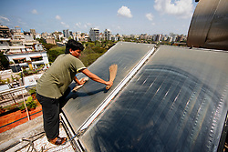 INDIA MUMBAI 29MAY10 - Housekeeper Narayan Bahadur (28) cleans solar thermal panels for a hot water installation on a roof of an apartment block in Juhu, Mumbai, India...jre/Photo by Jiri Rezac..© Jiri Rezac 2010