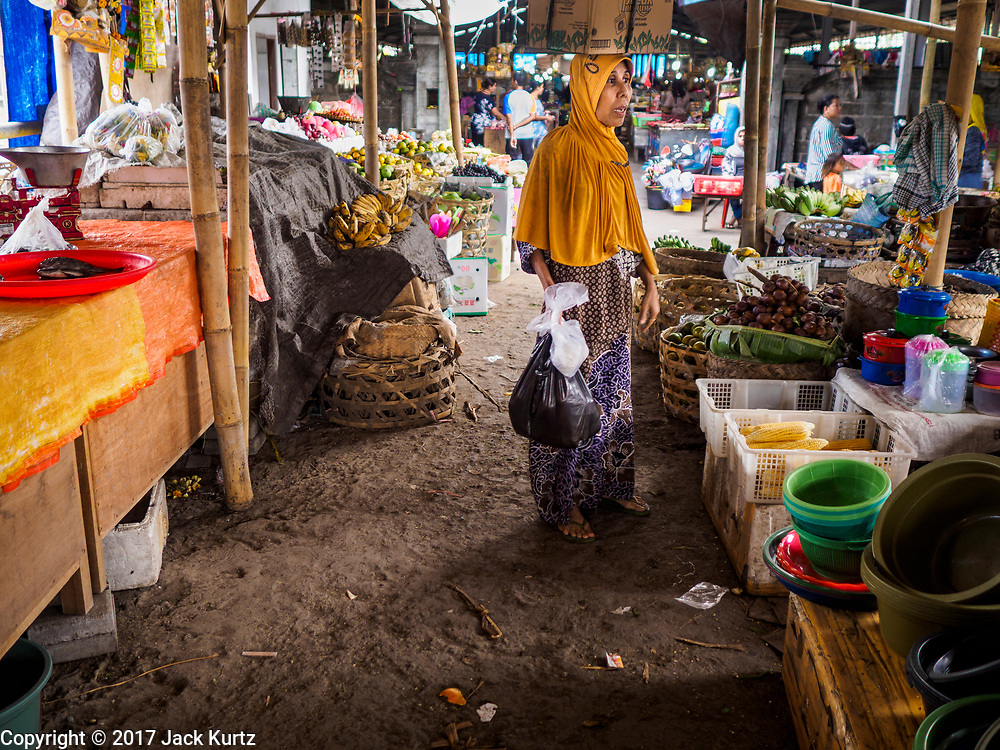 07 AUGUST 2017 - KECAMATAN, BALI, INDONESIA: A woman leaves the market in Kecamatan, in eastern Bali, after shopping. Bali's local markets are open on an every three day rotating schedule because venders travel from town to town. Before modern refrigeration and convenience stores became common place on Bali, markets were thriving community gatherings. Fewer people shop at markets now as more and more consumers go to convenience stores and more families have refrigerators.     PHOTO BY JACK KURTZ