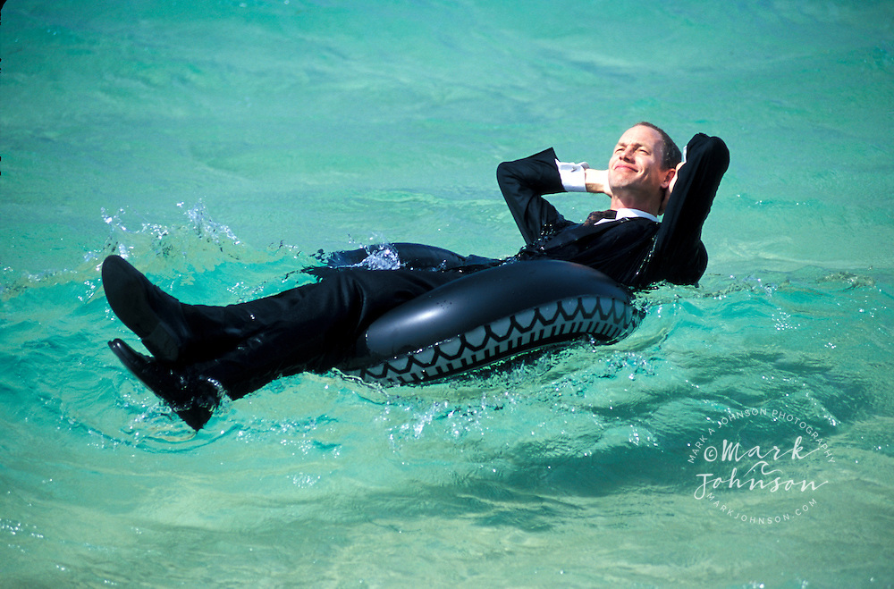 Businessman relaxing on swim ring in sea