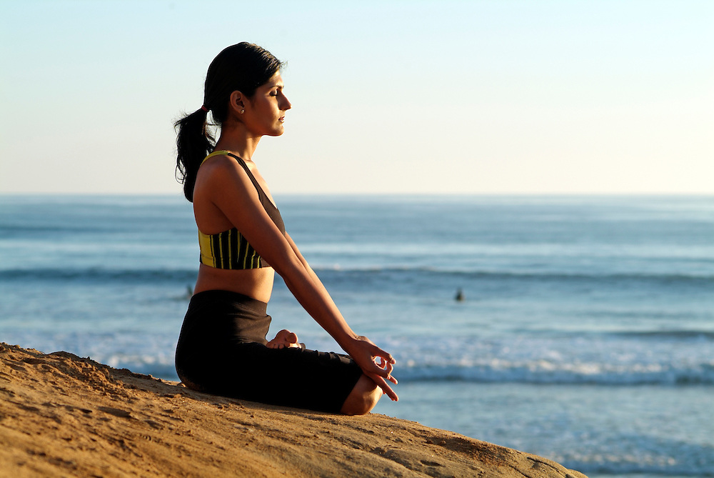 Wellness image of young woman meditating on cliff over looking ocean at sunset
