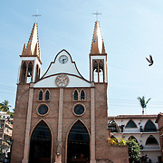 A woman walks under a church in Puerto Vallarta, Mexico. Photo by William Drumm.