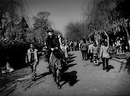 Tibetan horsemen lead Chinese tourists into the Naxi old city atop ponies for a fee.  Lijiang, Yunnan, China.