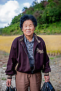 Portrait of a woman standing in front of a rice field at the Gangwon-do province a few kilometers from the Demilitarised Zone (DMZ) which is deviding North and South Korea.