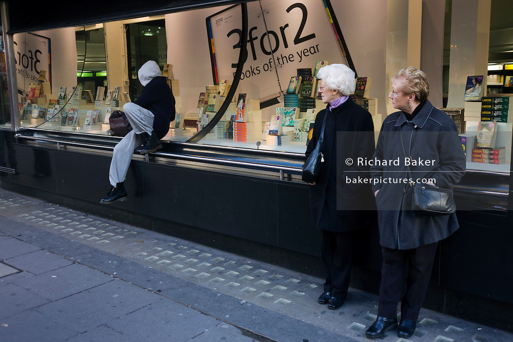 A hoodie youth jumps down from Waterstone's bookshop window ledge at London bus stop, watched by old ladies.