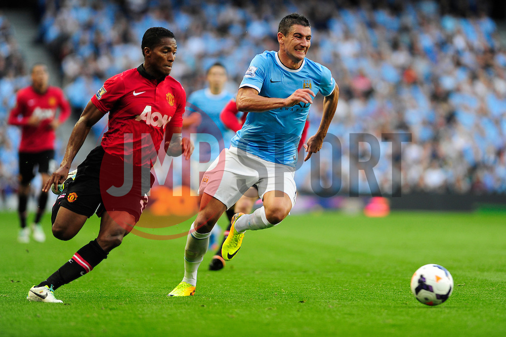 Manchester City's Aleksandar Kolarov and Manchester United's Luis Antonio Valencia chase after the ball - Photo mandatory by-line: Dougie Allward/JMP - Tel: Mobile: 07966 386802 22/09/2013 - SPORT - FOOTBALL - City of Manchester Stadium - Manchester - Manchester City V Manchester United - Barclays Premier League