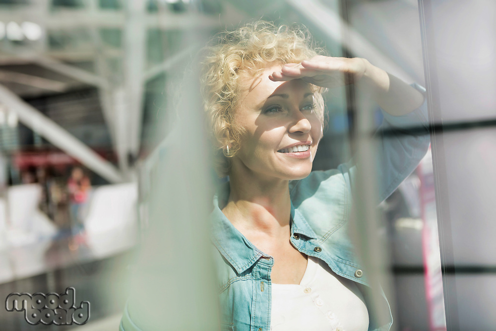 Portrait of mature woman covering her eyes from sunlight while looking through the window in airport