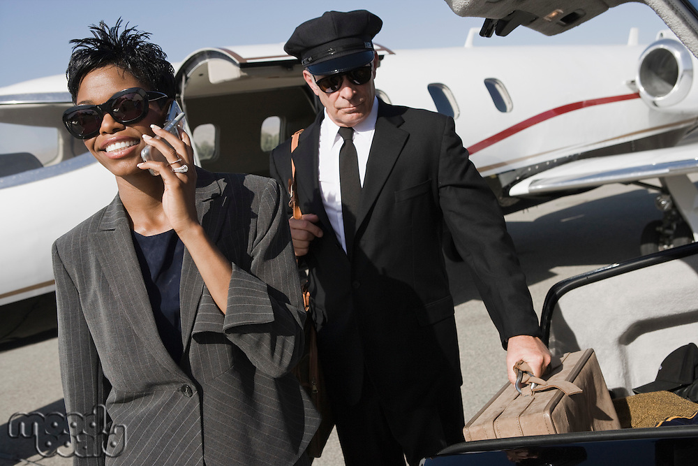 Mid-adult businesswoman talking on phone while chauffeur is waiting