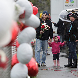 "Chris Green (L) and Angela Green (3rd L), both graduates of Marysville-Pilchuck High School, walk with their daughter Dorothy, 2, as they take flowers to the makeshift memorial outside the school in Marysville, Washington October 25, 2014. Relatives of a Washington state teen accused of a high school shooting rampage said on Saturday that they were living in a ""nightmare"" and struggling to understand why the boy targeted his two cousins and several friends before killing himself. One girl was killed and four other freshman students were severely wounded in Friday's morning rampage inside the cafeteria at Marysville-Pilchuck High School, north of Seattle. REUTERS/Jason Redmond (UNITED STATES - Tags: CRIME LAW SOCIETY EDUCATION)"
