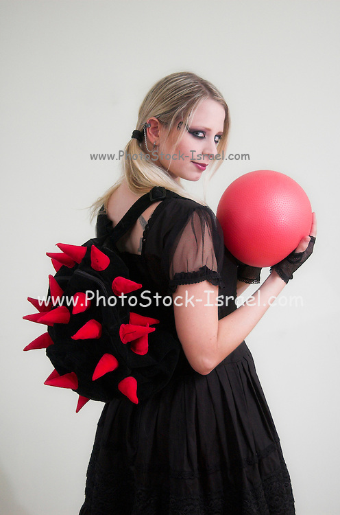A model wearing lolita style clothes playing with a ball