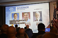 "Garden City, New York, USA. November 6, 2018. With 48% of votes in, Governor Andrew Cuomo is projected as winning re-election, over Marc Molinaro and Howie Hawkins. News 12 Long Island ""Island Vote 2018"" - projected on large screen - shows how candidates are doing in votes counted so far, as Nassau County Democrats watch Election Day results at Garden City Hotel, Long Island."
