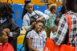 De-Ja Heyliger sits to have her hair styled by CAHS cosmetology student Andrea George.  Project Homeless Connect  connects those in need of support with vital resources and services.  St. Thomas, USVI.  4 December 2015.  © Aisha-Zakiya Boyd