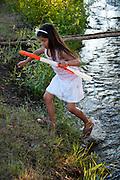 Yakima Indian children running in creek with toy guns