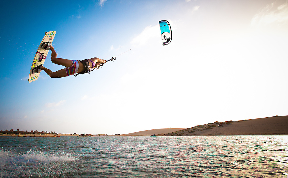 9 time world champion Kristin Boese leaps into the air kiteboarding in a lagoon in the Cape Verdes.