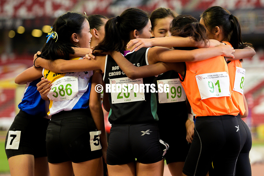C Division girls' 100m finalists hug after the race. (Photo © Eileen Chew/Red Sports)