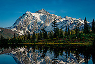"Mount Shuksan is a glaciated massif in the North Cascades National Park. Shuksan rises to 9,131 feet in Whatcom County, Washington immediately to the east of Mount Baker, and 11.6 miles south of the Canada–US border. The mountain's name Shuksan is derived from the Lummi word šéqsən, said to mean ""high peak""."