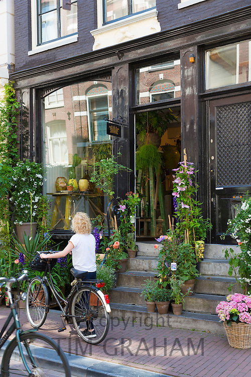 Woman with bicycle passes traditional florist shop in the Nine Streets - De Negen Straatjes - 9 Streets district of Jordaan, Amsterdam