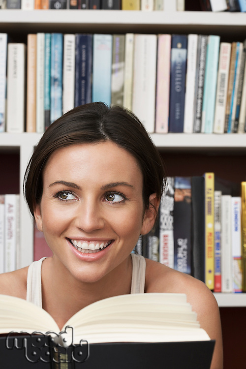 Young woman holding book by bookshelf smiling