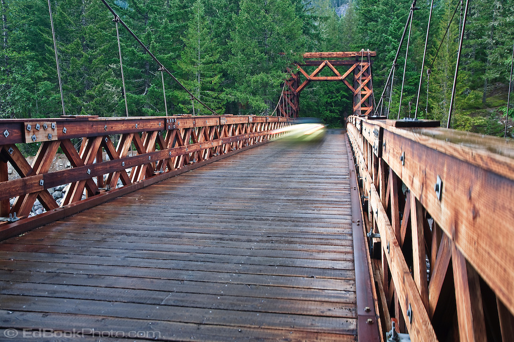 A vehicle crosses the Nisqually River wooden suspension bridge at Longmire village in Mount Rainier National Park, WA USA