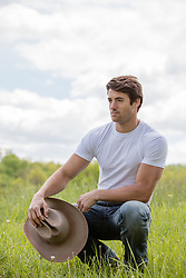 cowboy squatting down in a field