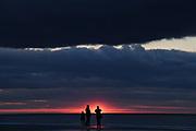 A family watches a stormy sunrise over the Atlantic Ocean on Coligny Public Beach in Hilton Head Island, South Carolina.