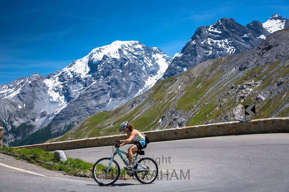 Female yclist rides Scott British mountain bike uphill on The Stelvio Pass, Passo dello Stelvio, Stilfser Joch, in the Alps, Italy