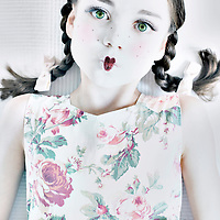 Young girl with brunette hair in plait and green eyes wearing white floral dress