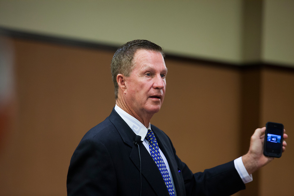 Doug Manchester, a real estate developer and publisher of U-T San Diego, shows how he can pull U-T TV up on his phone while speaking to a crowd of real estate professionals and students at San Diego State University on Thursday, Oct. 18, 2012.