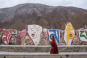 A Buddhist nun walks around the Gyanak mani wall in Yushu prefecture, Tibet (Qinghai, China).