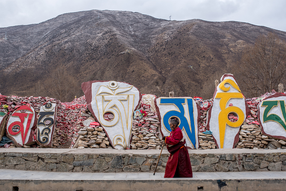 A Buddhist nun walks around the Gyanak mani wall in Yushu prefecture, Tibet (Qinghai, China).