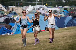 Image ©Licensed to i-Images Picture Agency . 20/07/2014 . Henham Park , Suffolk , United Kingdom . Wellies out - women cross from the camp site to the festival for the final day of music and events . The Latitude Festival of music and arts . Picture by Joel Goodman/i-Images