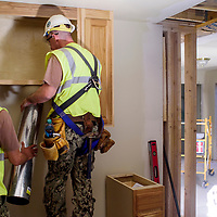 Harvie Ho, left, and Trip Woolf install a ventilation shaft in a home at the Southwest Indian Foundation in Gallup July 26.