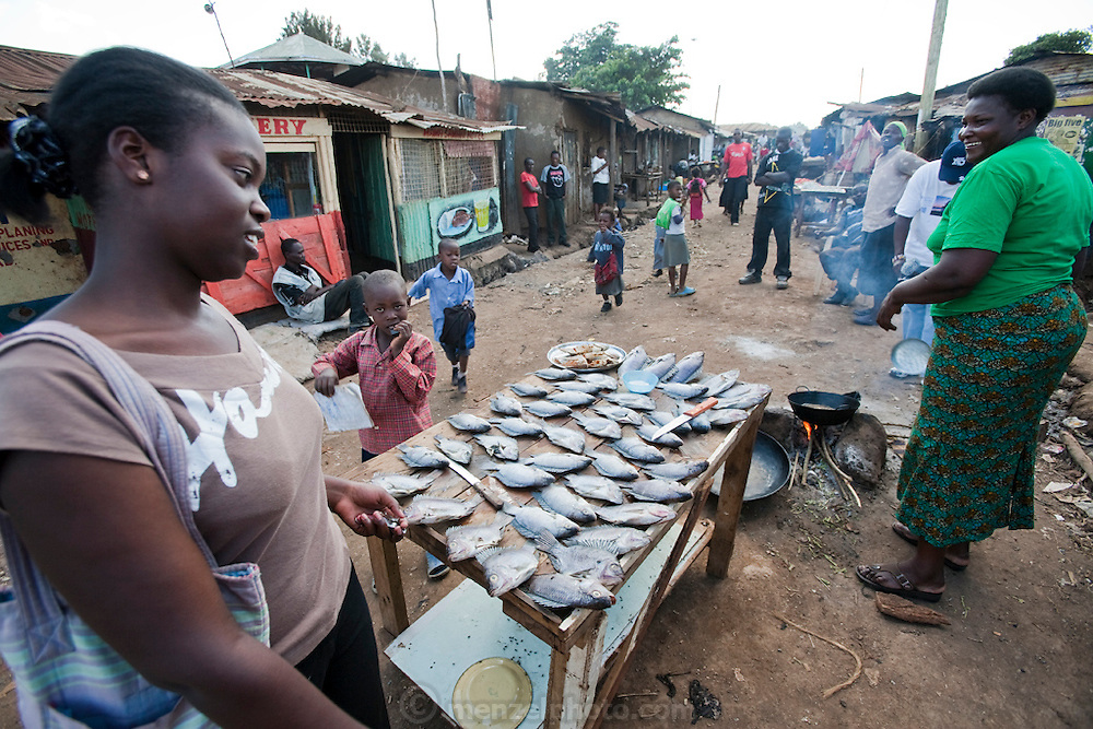 Roseline Amondi (right), a microloan recipient and mother of four, fries tilapia for sale in the Kibera slum in Nairobi, Kenya as her daughter looks on. (Roseline Amondi is featured in the book What I Eat: Around the World in 80 Diets.) MODEL RELEASED.