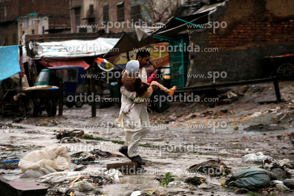 A man carries a child as he crosses a waterlogged street after heavy rain in northwest Pakistan's Peshawar, Feb. 25, 2015. At least two women were killed as a roof of a house collapsed in Peshawar. Heavy rains have wreaked havoc in different areas of Kashmir, Khyber Pakhtunkhwa and Gilgit-Baltistan on Wednesday, local media reported. EXPA Pictures &copy; 2015, PhotoCredit: EXPA/ Photoshot/ Umar Qayyum<br /> <br /> *****ATTENTION - for AUT, SLO, CRO, SRB, BIH, MAZ only*****