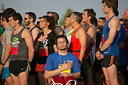 John Michalko, center, listens to the National Anthem before the Corporate Challenge on the campus of RIT on Tuesday, May 24, 2016.