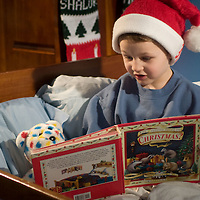 boy reading a christmas story to his teddy bear