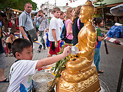 "26 JUNE 2011 - CHIANG MAI, THAILAND:  A boy bathes a statue of the Buddha to ""make merit"" in the ""Walking Street"" market in Chiang Mai, Thailand. The Walking Street market is a weekly, Sunday night, market along Ratchadamnoen Street in Chiang Mai.   PHOTO BY JACK KURTZ"