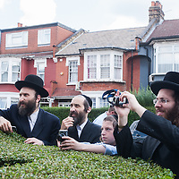 London, UK - 7 August 2014: members of the Orthodox Jewish community watches the Mayor Boris Johnson leaving with his bike after meeting Rabbi Oscher Schapiro in Stamford Hill, London