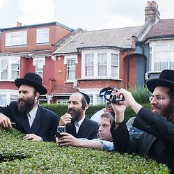 London, UK - 7 August 2014: members of the Orthodox Jewish community watches the Mayor Boris Johnson leaving with his bike after meeting Rabbi Oscher Schapiro in Stamford Hill, London