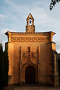 Low angle view of the facade of Capella de Sant Jordi, late 15th century, Monestir de Poblet, 1151, Vimbodi, Catalonia, Spain, pictured on May 20, 2006, in the warm evening light. The Capella has late gothic ornaments, including two emblems and a small belfry sitting on top. The Monastery of Poblet belongs to the Cistercian Order and was founded by French monks. Originally, Cistercian architecture, like the rules of the order, was frugal. But continuous additions  including late Gothic and Baroque, eventually made Poblet one of the largest monasteries in Spain which was later used as a fortress and royal palace. It was closed in 1835 by the Spanish State but refounded in 1940 by Italian Cistercians. It is a UNESCO World Heritage Site. Picture by Manuel Cohen