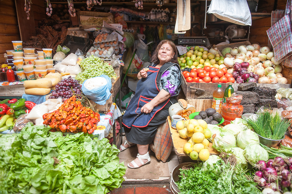 Woman vendor with fresh produce at a farmer's market in Puerto Montt, Chile