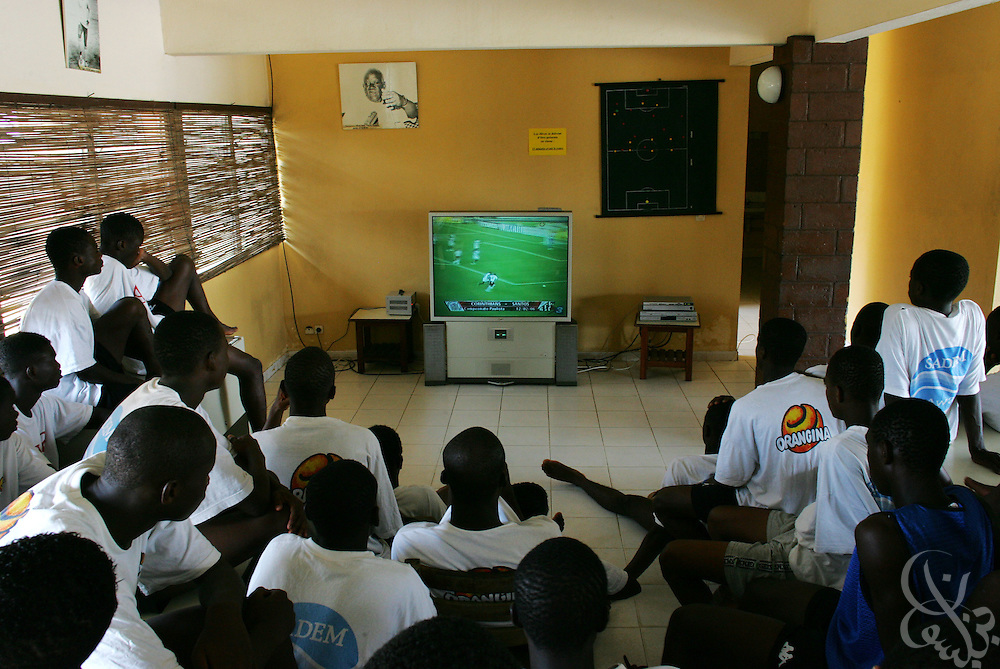 Teenage Ivorian football players watch television footage of European football games following their morning training session at the ASEC football academy February 16, 2006 in Abidjan, Côte d'Ivoire. ASEC academy has an established history of producing top notch footballers who go on to play in the top European football leagues.