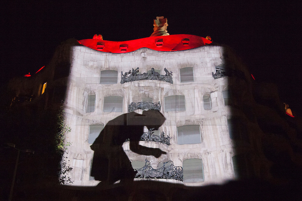 """© Licensed to London News Pictures. 1 December 2012. Barcelona, Spain. Show """"Emocions en moviment"""" with 8 live dancers and their images on the façade of La Pedrera. In 1912, La Pedrera (Casa Mila), Barcelona's iconic landmark by architect Antoni Gaudi was finished  To celebrate 100 years of La Pedrera, Barcelona citizens were treated to a free tour of the building where 150 dancers and musicians performed around every corner and on the roof. Later, images were projected onto the façade of the building with live dancers interacting with them. Photo credit: Bettina Strenske/LNP"""