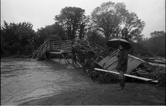 "Flooding at the Dodder..1986..26.08.1986..08.26.1986..28th August 1986..As a result of Hurricane Charly (Charlie) heavy overnight rainfall was the cause of severe flooding in the Donnybrook/Ballsbridge areas of Dublin. In a period of just 12 hours it was stated that 8 inches of rain had fallen. The Dodder,long regarded as a ""Flashy"" river, burst its banks and caused great hardship to families in the 300 or so homes which were flooded. Council workers and the Fire Brigades did their best to try and alleviate some of the problems by removing debris and pumping out some of the homes affected..Note: ""Flashy"" is a term given to a river which is prone to flooding as a result of heavy or sustained rainfall...Image of a pedestrian braving the elements as he surveys the damage to the footbridge.Note the size of the trees which were carried by the flood."