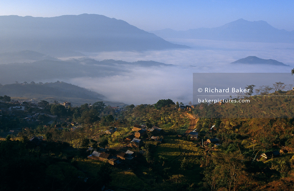 Aerial landscape of farms, villages, early mist-shrouded valleys and distant Himalayan mountains in Gorkha, Nepal.