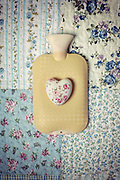 a hot-water bottle on a vintage bed with a floral heart