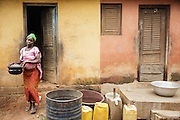 Christine Koné, 26, carries a cooking pot as she walk out of her home in the town of Katiola, Cote d'Ivoire on Friday July 12, 2013. Christine underwent FGM as a child and now suffers from incontinence. She says she would never allow her daughter to undergo the procedure.