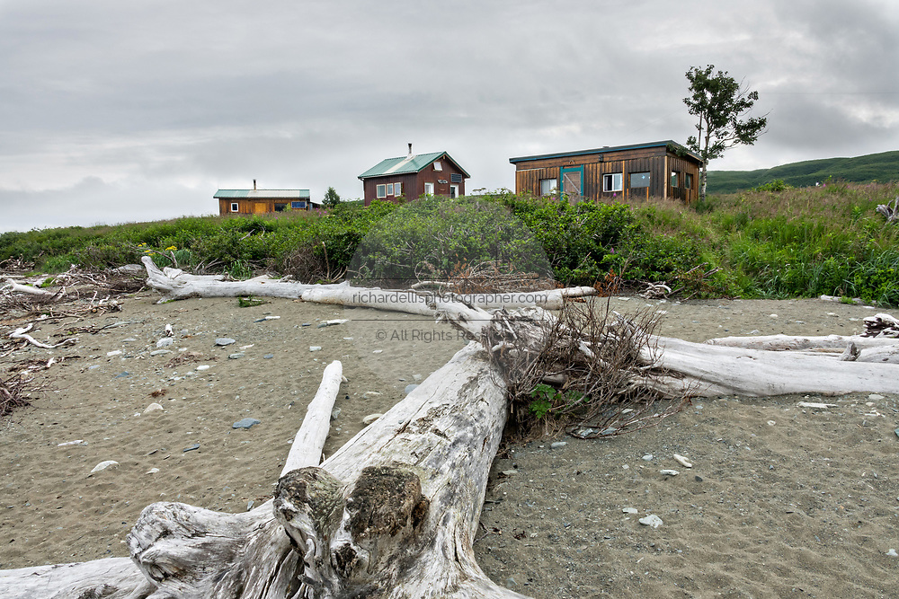The only three structures at the McNeil River State Game Sanctuary seen from the beach include two ranger cabins and the campsite cook cabin on the Cook Inlet, Alaska. The remote site is accessed only with a special permit and is the world's largest seasonal population of brown bears in their natural environment.