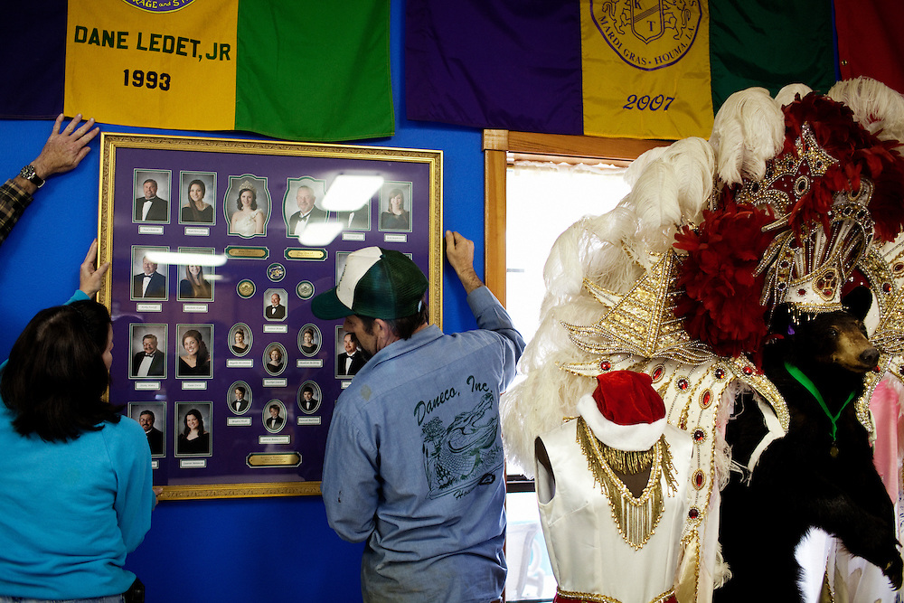"""Dane """"Peanut"""" Ledet Jr. his wife Dawn and brother-in-law Stephen Bonnecarrere work to hang a Mardi Gras picture on the wall of the game room at Daneco Alligator Farm in Houma, Louisiana on Friday, February 19, 2010."""