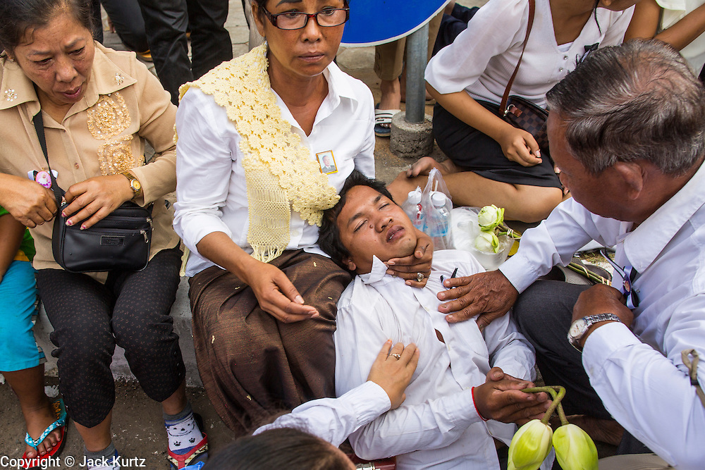 """01 FEBRUARY 2013 - PHNOM PENH, CAMBODIA: Cambodians reach to help a young man who collapsed in grief as the funeral procession of former Cambodian King Norodom Sihanouk passed him. The man was revived and stayed at the procession. Norodom Sihanouk (31 October 1922- 15 October 2012) was the King of Cambodia from 1941 to 1955 and again from 1993 to 2004. He was the effective ruler of Cambodia from 1953 to 1970. After his second abdication in 2004, he was given the honorific of """"The King-Father of Cambodia."""" Sihanouk died in Beijing, China, where he was receiving medical care, on Oct. 15, 2012. His cremation is will be on Feb. 4, 2013. Over a million people are expected to attend the service.    PHOTO BY JACK KURTZ"""