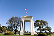 """The Peace Arch (1921) looking towards the United States.  Photographed from Peace Arch Provincial Park in Surrey, British Columbia, Canada.  The Peace Arch was built in 1921 to commemorate the 100 year anniversary of treaties at the end of the War of 1812 between the USA and Great Britain. One side states """"Children Of A Common Motherr"""", the other """"Brethren Dwelling Together In Unity""""."""